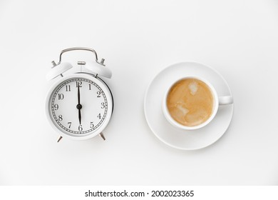 retro alarm clock and a cup of coffee on a white background. concept of early morning ascents. Timing. first shift at school or at work.