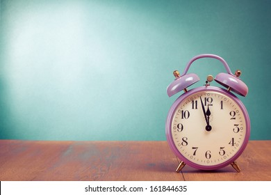 Retro alarm clock with five minutes to twelve o'clock