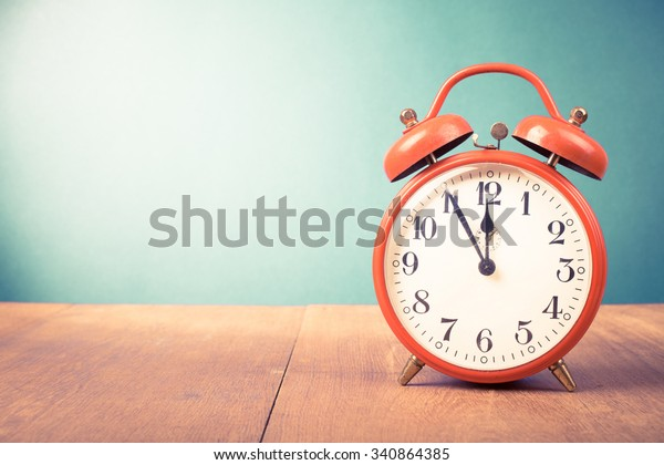 Retro alarm clock with five minutes to twelve o'clock. Old style filtered photo