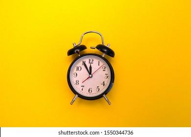 Retro alarm clock isolated on yellow background