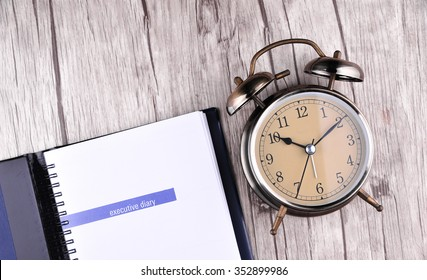 Retro Alarm Clock With Notebook Paper On Table
