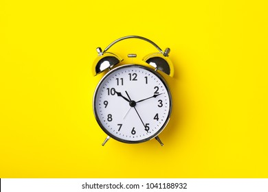 Retro alarm clock on bright yellow background