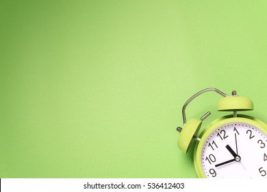Retro alarm clock on green background
