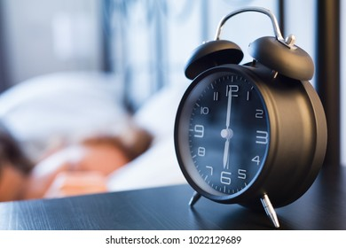 A retro alarm clock on a night stand next to a woman sleeping in bed. Closeup shot with shallow DOF, focus on the clock hands.
