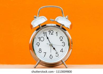 Retro alarm clock on orange background