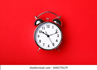 Retro alarm clock on red background