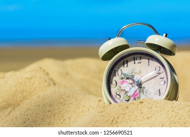 A retro alarm clock on a sand at the beach with golden sunlight and blue sky.