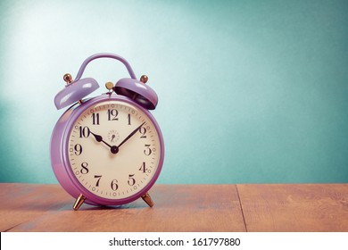 Retro alarm clock on table front mint green background