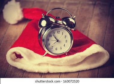retro alarm clock on table with christmas hat