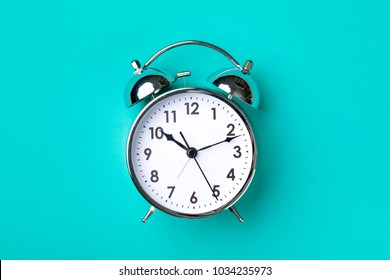 Retro alarm clock on turquoise background