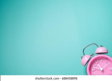 Retro alarm clock on turquoise background