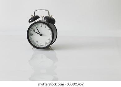 Retro alarm clock on white background, natural light, minimalism