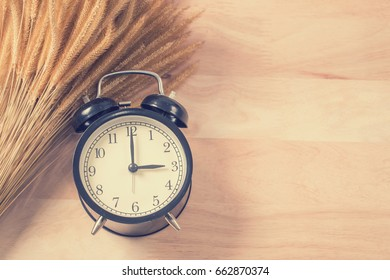 Retro alarm clock on wood background process vintage color
