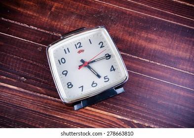 Retro alarm clock on wooden board background