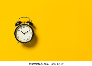 Retro alarm clock on yellow color background
