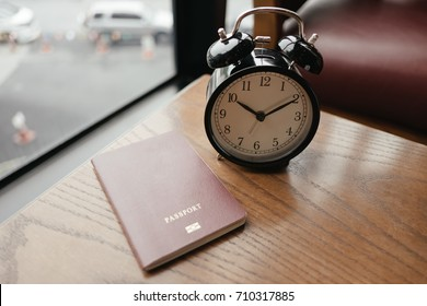 retro alarm clock placed beside passport on wooden table with window are background in morning. this image for business,interior,gadget,accessory,object,document concept
