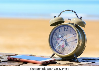 A retro alarm clock with a worn out mobile phone on a stone floor.  Sandy beach as the background.