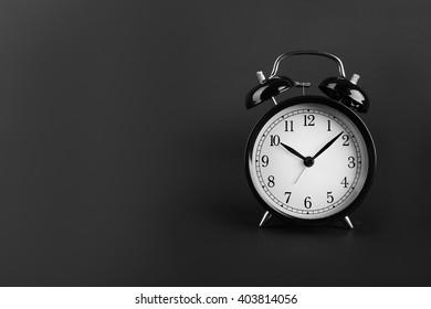 A retro alarm-clock on dark grey background.