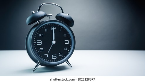 Retro analog alarm clock with bells showing midnight or noon with alarm set for seven o'clock.