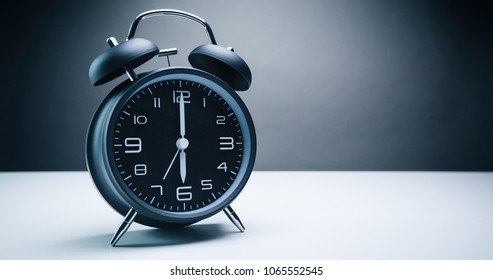 Retro analog alarm clock with bells showing six o'clock with alarm set for seven.