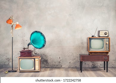 Retro analog CRT televisions, wooden TV stand with outdated amplifier, old radio receiver from 60s, classic gramophone, floor lamp front aged concrete wall background. Vintage style filtered photo