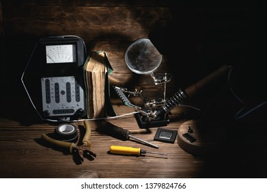 Retro analog voltmeter, soldering iron, book, microcircuit chip, pliers and screwdriver in the light of lamp on a brown wooden table background. Electrical works abstract background.