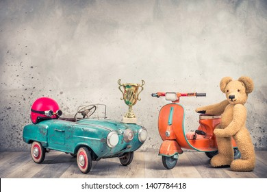 Retro antique aquamarine rusty pedal car from 60s, red helmet with goggles, race winner golden cup, old orange children's scooter and Teddy Bear plush toy front loft wall. Vintage style filtered photo
