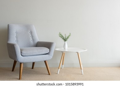 Retro armchair and small round table with rosemary in small vase against beige wall
