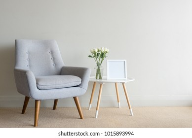 Retro armchair and small round table with roses in glass vase and blank square frame against beige wall