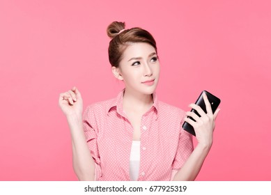 Retro asian business woman in colorful shirt holding a smartphone and looking to the side, beauty face, pink background.