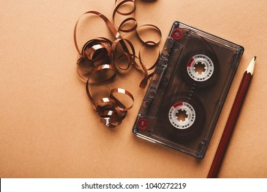 Retro audio cassette and pencil on light brown background. Top view on vintage tape and simple device for rewinding, copy space. Obsolete technology concept