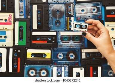 Retro audio cassette tapes on blue background. Top view on vintage media devices, female hand holding one small tape, copy space on labels, flat lay