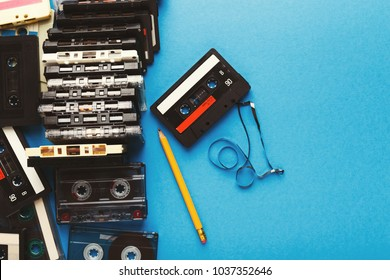 Retro audio cassettes and pencil on blue background. Top view on vintage tapes and simple device for rewinding, copy space. Obsolete technology concept