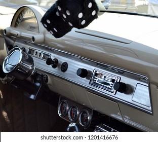 Retro automobile dash, tan and silver, with black fuzzy dice.
