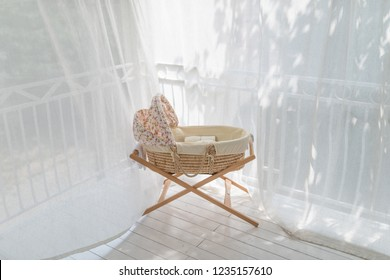 Retro baby crib on terrace rounded with curtain at sunny day
