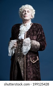 Retro baroque man with white wig standing and looking arrogant. Studio shot against blue.