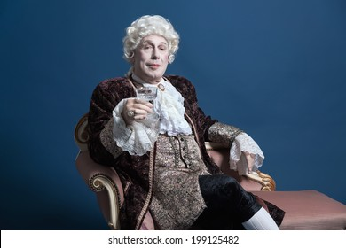 Retro baroque man with white wig holding a wine glass sitting on antique couch. Studio shot against blue.