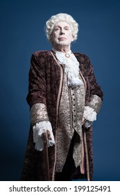 Retro baroque man with white wig standing with walking stick arrogant looking. Studio shot against blue.