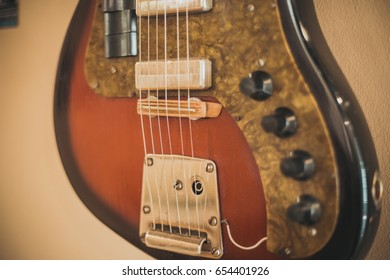 Retro bass guitar in vintage style on shelves in a musical instrument store
