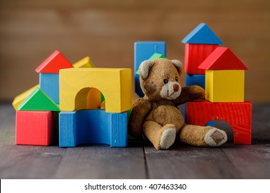 Retro Bear toy alone on wooden floor with bilding blocks