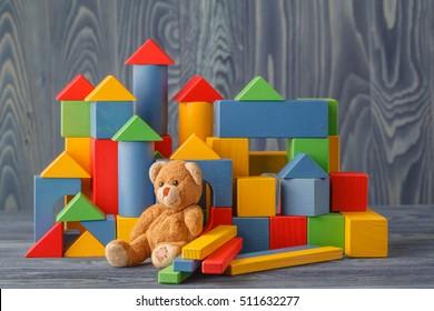 Retro Bear toy alone on wooden floor with bilding blocks