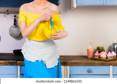 Retro beauty pin up girl housewife wearing colorful top, skirt and white apron holding whipper and bowl making sweets in the kitchen with blue cabinets and utensils and cupcakes with milkshake.