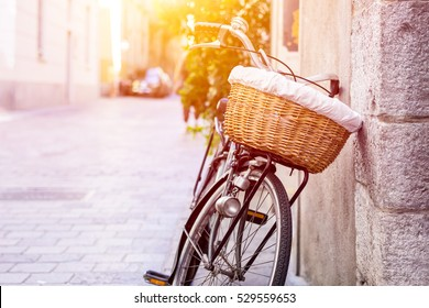 Retro bicycle with a basket leaning against a wall. Cycle on stone medieval street in historical center of Como, Italy. Retro cycle on blurred background with copy space area for a text.