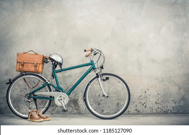 Retro bicycle from circa 90s with aged leather mailman's bag, helmet and old sneakers front concrete wall background. Vintage style filtered photo