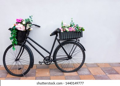 Retro bicycle as a flowerbed decoration outside element. Black aged bike stays against the wall with two garden baskets with beauty flowers. Art decor object
