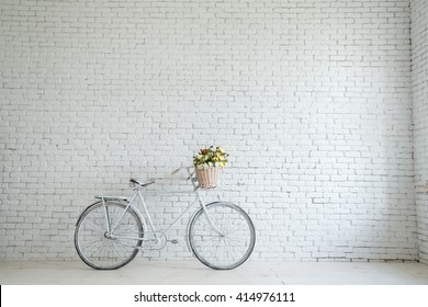 Retro bicycle on roadside with vintage brick wall background,