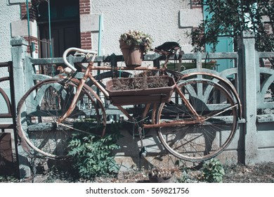 Retro bike flowerpot. Real French village. Real Vintage atmospheric flowers and bicycle in Europe