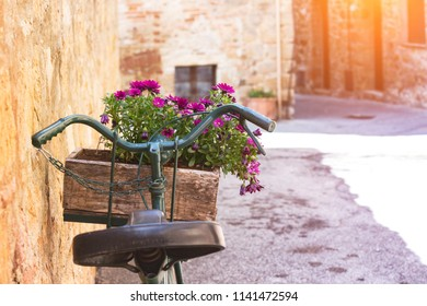 retro bike with flowers standing on a street of small italian town