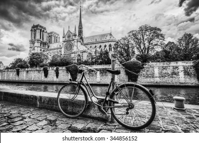 Retro bike next to Notre Dame Cathedral in Paris, France and the Seine river. Black and white vintage