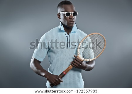 c35e37d05a5 Retro black african tennis player wearing blue shirt and white sunglasses.  Holding vintage racket.